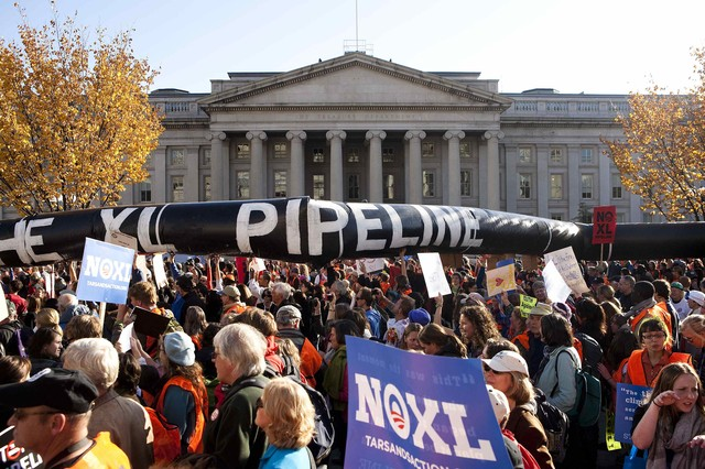 File photo of demonstrators carrying a giant mock pipeline while calling for the cancellation of the Keystone XL pipeline during a rally in Washington